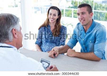 Smiling doctor showing ultrasound scan to the couple in medical office