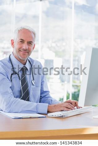 Smiling doctor typing on his computer and sitting behind his desk - stock photo