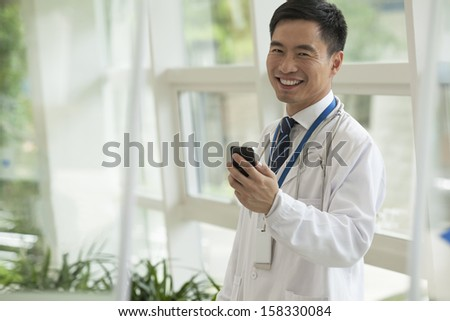 Smiling doctor using his phone in hospital lobby - stock photo