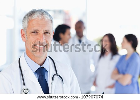 Smiling doctor waiting for his team while standing upright - stock photo