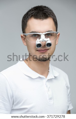 Smiling doctor with dental binocular loupes on his face on the gray backround. He is in a white t-shirt. Studio photo. Vertical. - stock photo
