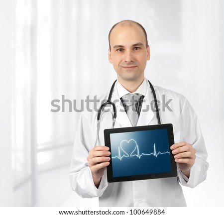 Smiling doctor with hearts beat diagram on a tablet computer - stock photo