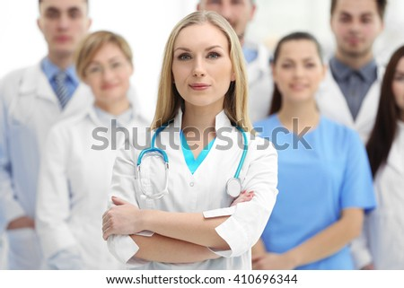 Smiling doctor with medical workers standing in hospital - stock photo