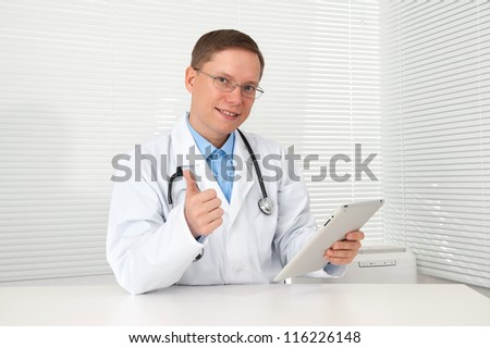 Smiling doctor with tablet computer