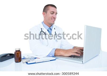 Smiling doctor working on his laptop on a white background
