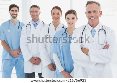 Smiling doctors all standing together and looking at the camera