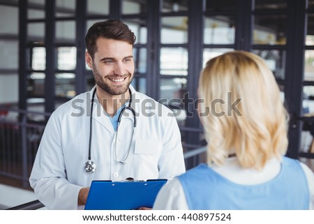 Smiling doctors discussing while standing at hospital - stock photo