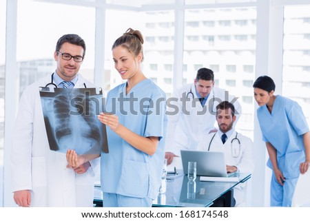 Smiling doctors examining x-ray with colleagues using laptop behind in a medical office