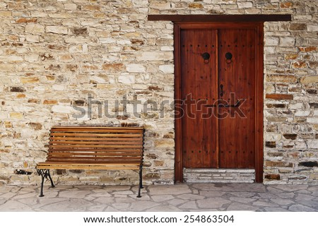Smiling door and bench. Facade of yellow brick house in Cyprus  - stock photo