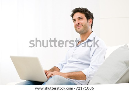 Smiling dreaming young man looking up while working at laptop computer - stock photo