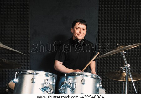 Smiling drummer plays on drum set. Playing on drums musician loks at camera and smiles. Smiling drummer with drumsticks in his hands - stock photo