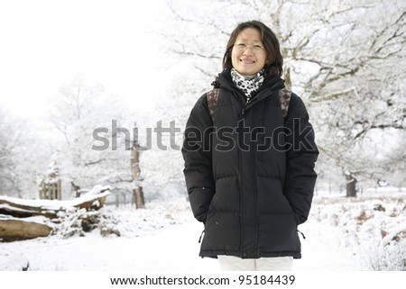 Smiling East Asian Woman Looking the Camera in snow covered Richmond Park - stock photo