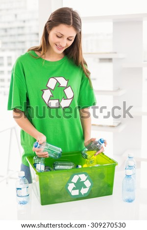 Smiling eco-minded brunette holding recycling bottles in the office