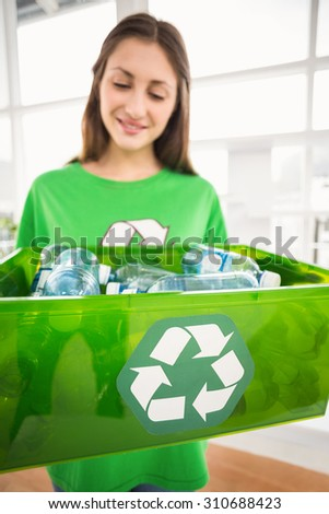 Smiling eco-minded brunette showing recycling box in the office