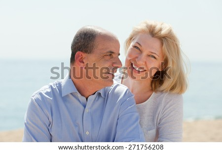 Smiling elderly couple having honeymoon at sea shore in warm season - stock photo