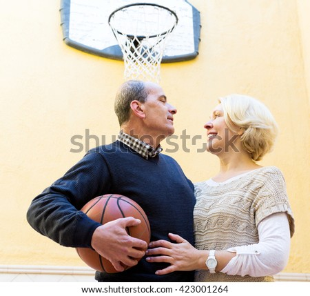 Smiling elderly couple playing with ball in yard