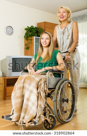 Smiling elderly doctor visiting handicapped young girl at home - stock photo