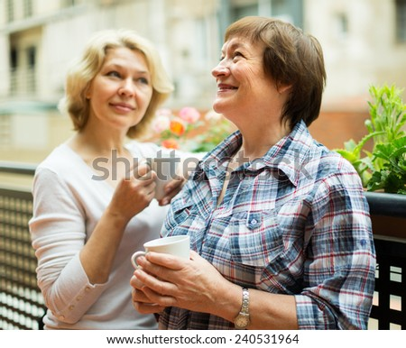 Smiling elderly female friends staying on balcony with cup of coffee - stock photo