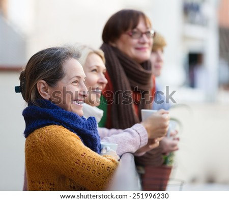 Smiling elderly female in warm clothes having cup of hot tea on terrace. Focus on brunette woman - stock photo