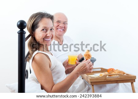 Smiling elderly husband brings his wife breakfast in bed. - stock photo