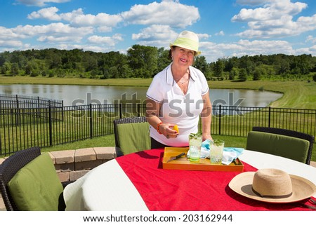 Smiling elderly lady in a trendy sunhat standing at a garden table on an outdoor patio covered in a red cloth preparing glasses of iced water with fresh lemon and mint in scenic countryside