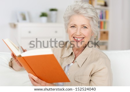 Smiling elderly lady reading a book while sitting in her living room pausing to look and smile at the camera - stock photo