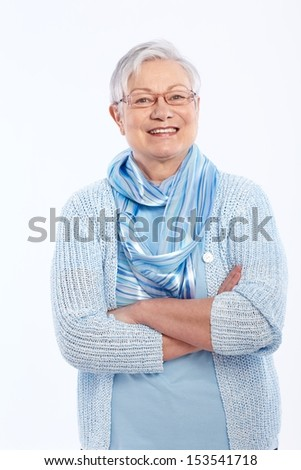 Smiling elderly lady standing arms crossed, looking at camera. - stock photo