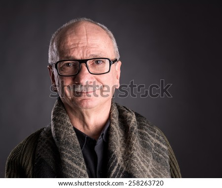 Smiling elderly man in glasses on a dark background - stock photo