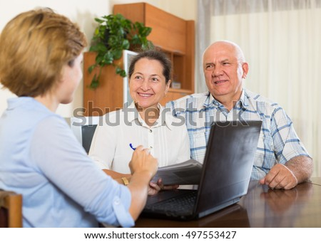 Smiling elderly  mature couple discussing for agent or employee of  company at home
