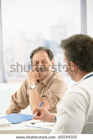 Smiling elderly patient sitting at doctor's office on consultation.? - stock photo