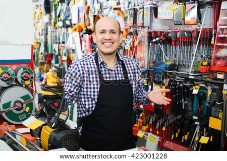 Smiling elderly seller posing near electric compressor in household store