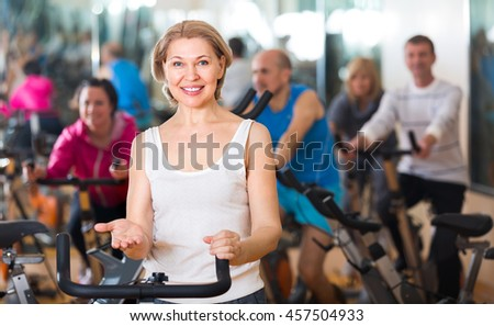 Smiling elderly woman on fitness cycle in a gym