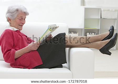 Smiling elderly woman reading on a sofa relaxing with her bare feet over the arm couch - stock photo