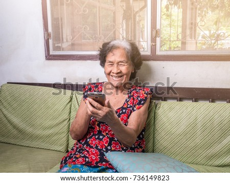Smiling elderly woman while looking at mobile phone sitting on sofa bed