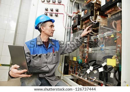 Smiling electrician at work checking wire with drawing inspecting high voltage power electric line distribution fuseboard - stock photo