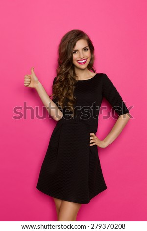 Smiling elegance young woman in black mini dress posing with hand on hip and showing thumb up. Three quarter length studio shot on pink background. - stock photo