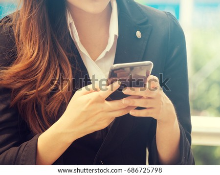 Smiling Elegant Asian Business Woman Using Smartphone in ourdoor scenes.woman use smartphone for internet shopping online or eCommerce.