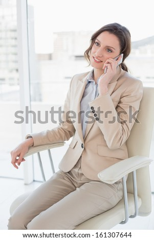 Smiling elegant businesswoman using mobile phone in a bright office