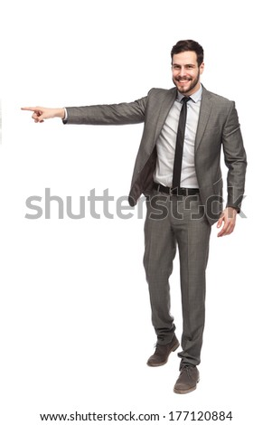 smiling elegant sales man pointing one direction on white background - stock photo