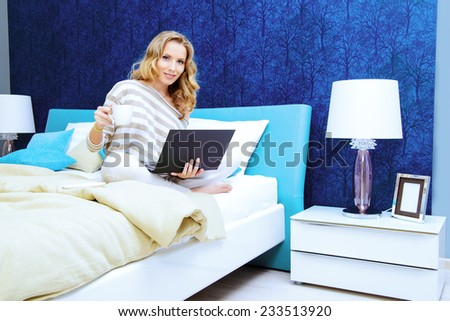 Smiling elegant woman sitting on a bed with her laptop computer in a bedroom. Home interior, furniture. Lifestyle. - stock photo