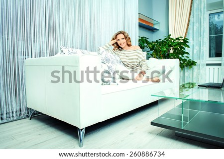 Smiling elegant woman sitting on a sofa in a living room. Home interior, furniture. Lifestyle. - stock photo
