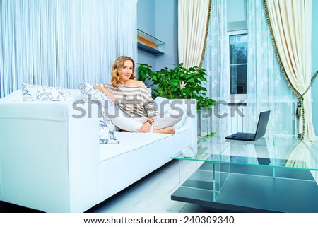 Smiling elegant woman sitting on a sofa with her laptop computer in a bedroom. Home interior, furniture. Lifestyle. - stock photo
