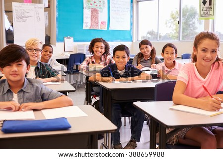 Smiling elementary school kids sitting at desks in classroom - stock photo