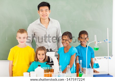 smiling elementary school students and teacher in chemistry class