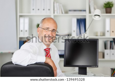 smiling employee sitting at desk and looking back - stock photo