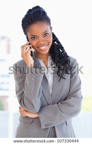 Smiling employee standing upright seriously and talking on a phone with her arms crossed