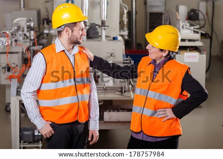 Smiling employees discussing at production area,horizontal