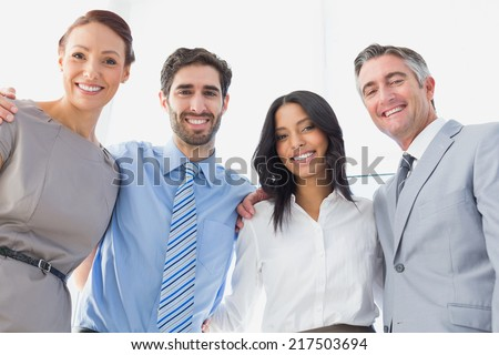 Smiling employees standing all together at work - stock photo