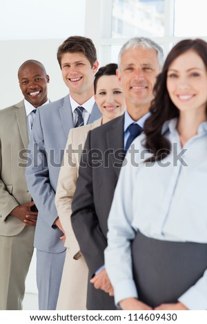 Smiling employees standing in the back while laughing and following their team