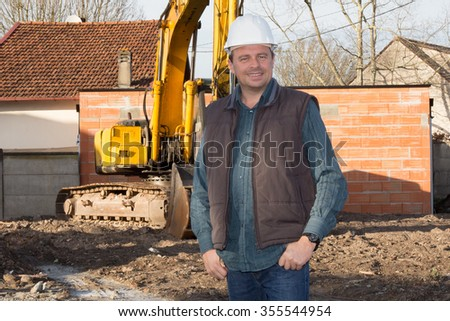Smiling Engineer  at construction site with blue sky background.